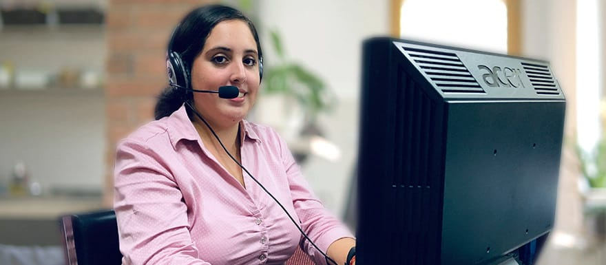 Medical Biller and Coder talking on a headset and using a computer.